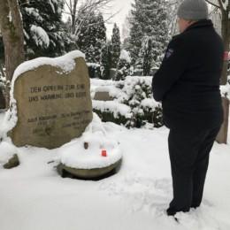Auf dem Bild ist der 1. Vorsitzende, Carsten Georg, vor dem Ehrenmal für die Opfer des Nationalsozialismus zu sehen. Er hat eine Kerze angezündet und gedenkt der Opfer.